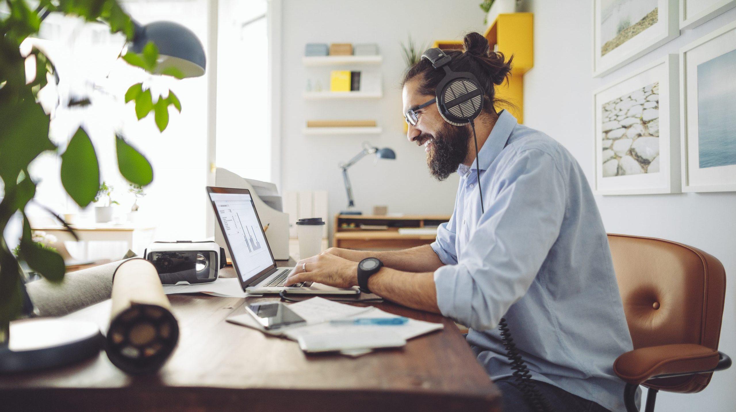 Homme barbu travaille sur bureau